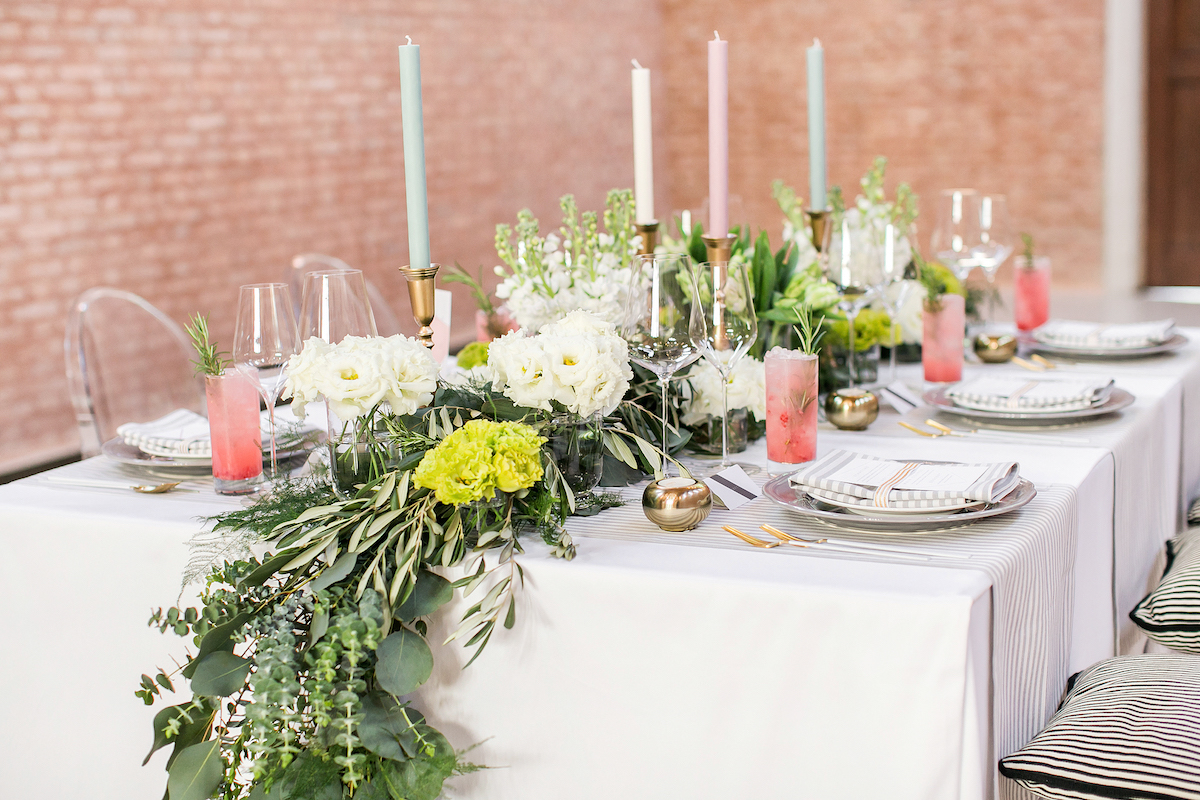 Image of a wedding table set up with green foliage, while and pink details at JW Marriott Venice