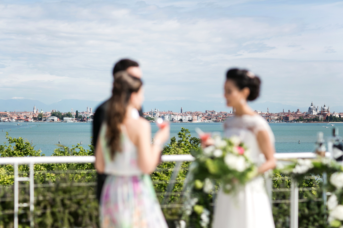 Image of a bride and groom with a wedding guest in Venice
