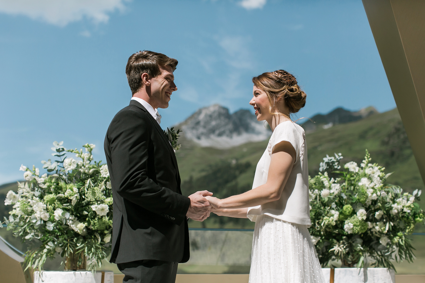 Bride and groom exchanging vows at an intimate outdoor ceremony at Intercontinental Davos with mountains as a backdrop styled by international wedding planner Elisabetta White