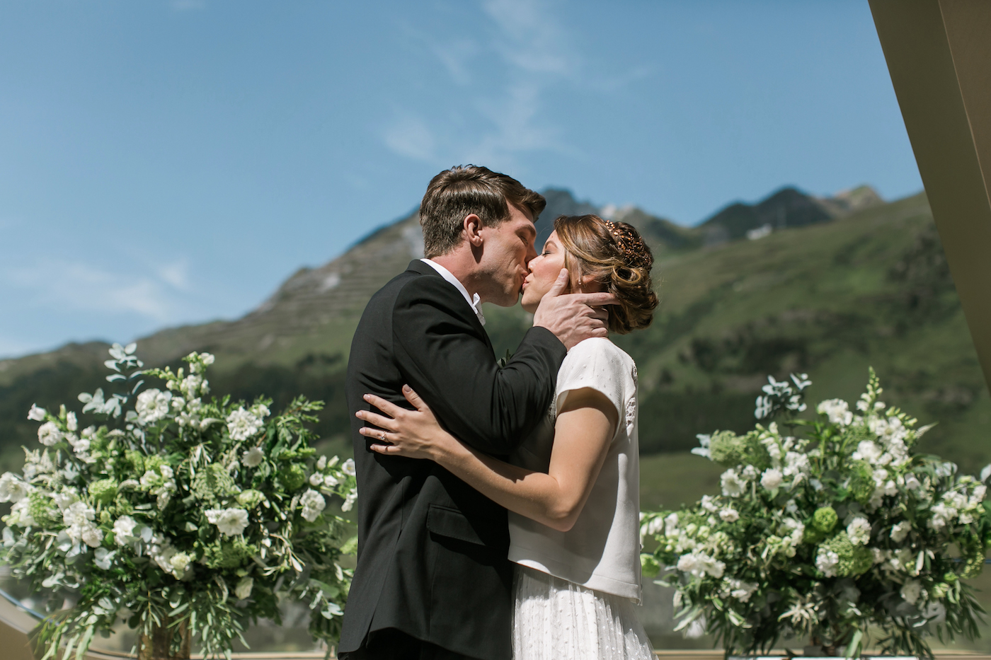 Bride and groom kissing with mountain backdrop