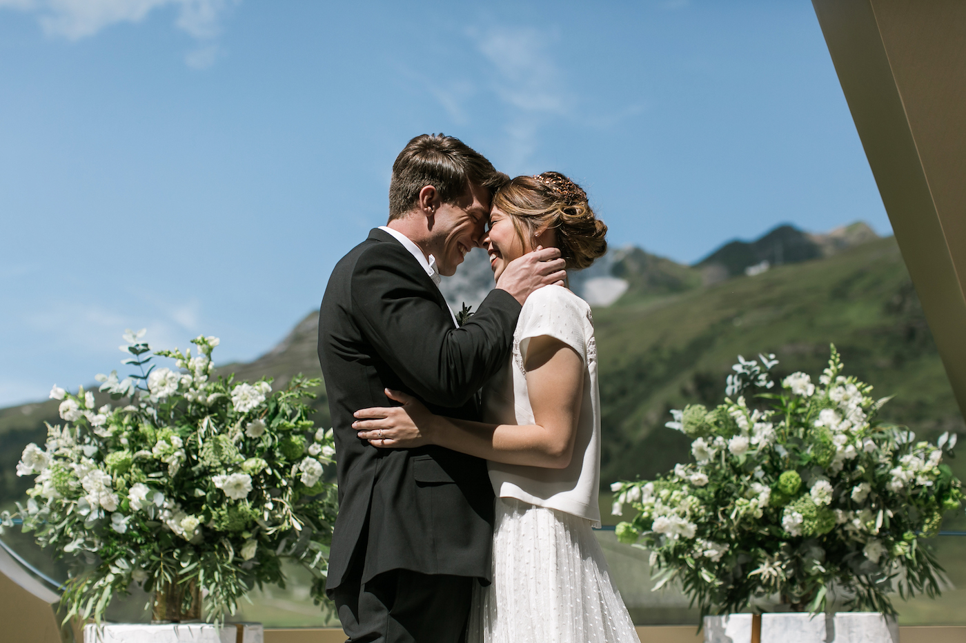 Bride and groom kissing with Swiss alps backdrop