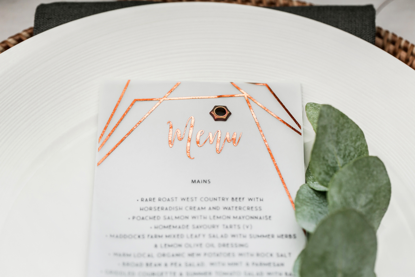Copper foiled menu cards over a plate styled by international wedding planner Elisabetta White