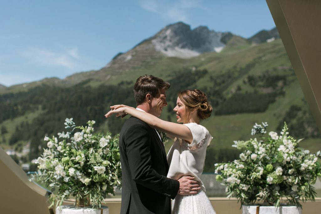 Bride and groom hugging with Swiss Alps backdrop
