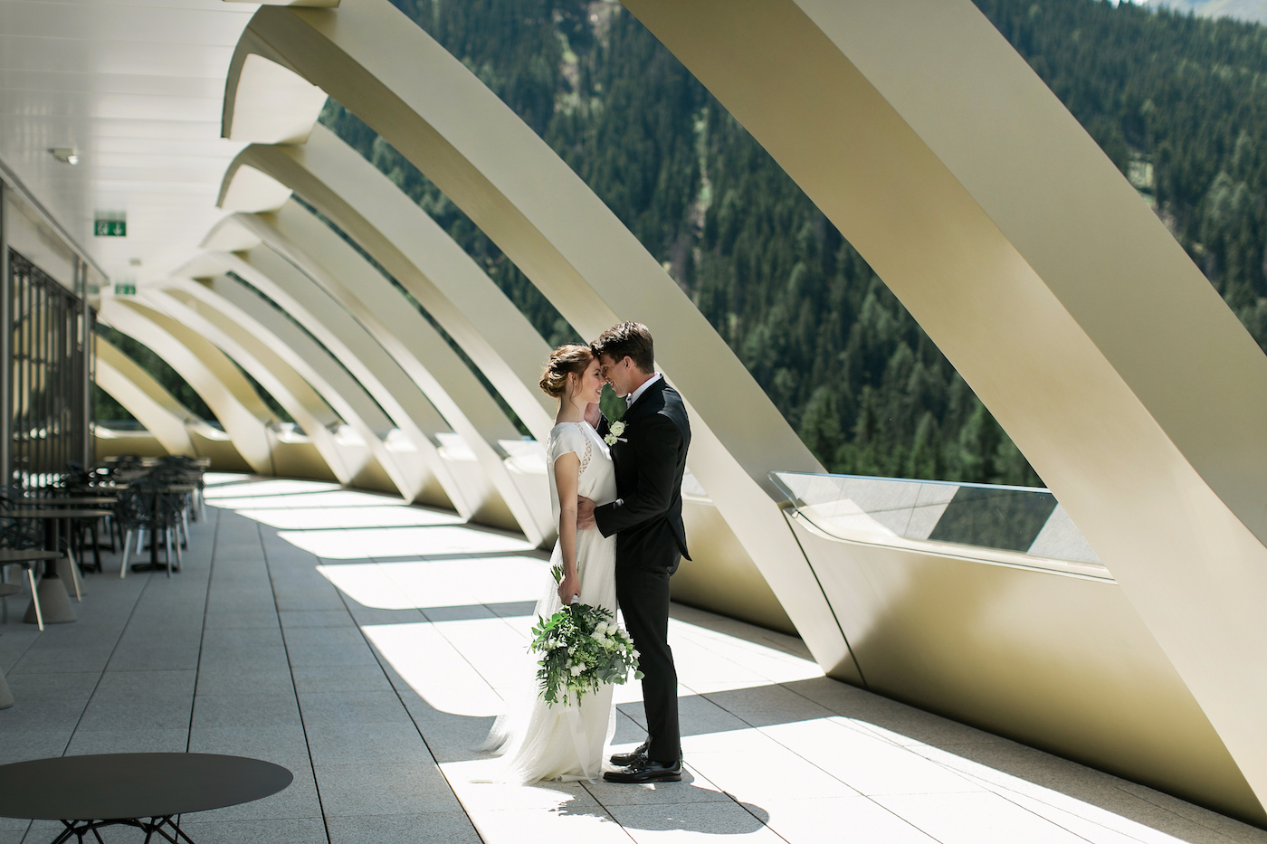 Bride and groom on the modernist terrace of Intercontinental Hotel Davos styled by international wedding planner Elisabetta White