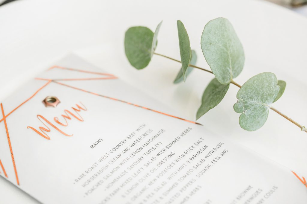 Copper foiled menu cards and eucalyptus leaf styled by international wedding planner Elisabetta White