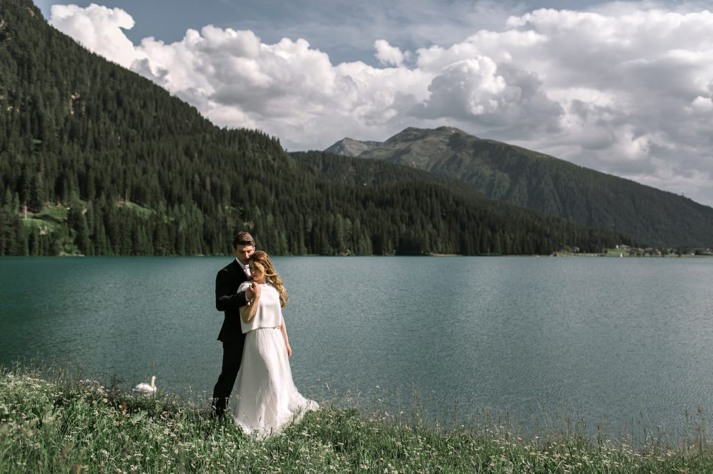 Adventurous bride and groom hugging in front of Davos lake styled by international wedding planner Elisabetta White