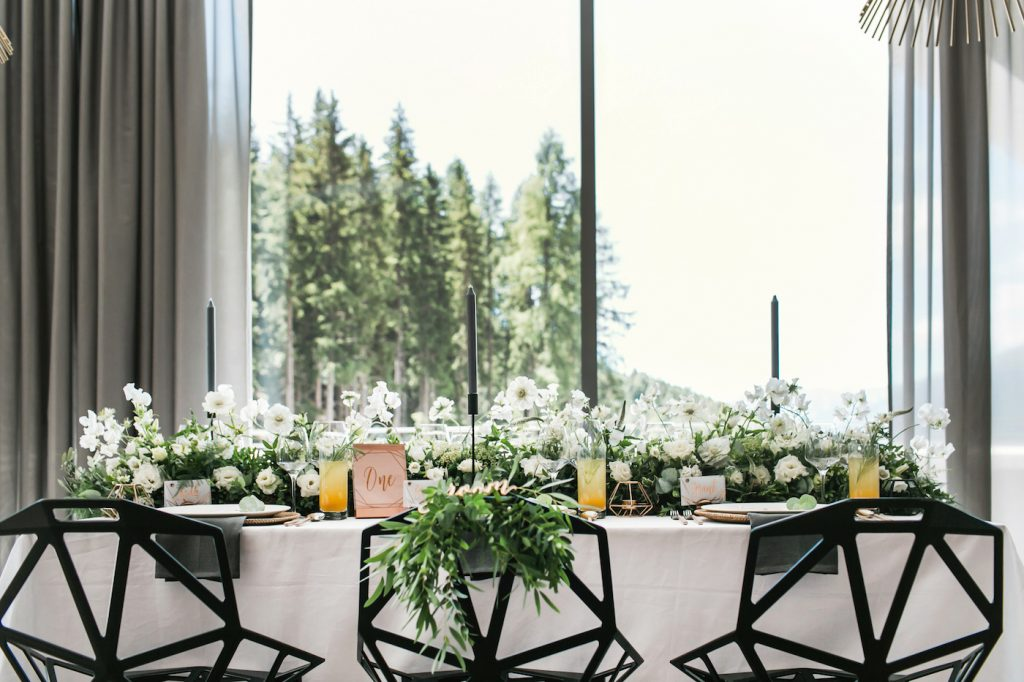 Modern intimate wedding table with modern black chairs and lots of foliage styled by international wedding planner Elisabetta White