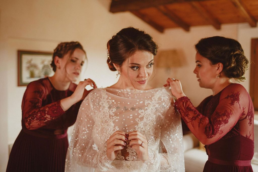 Bridesmaids helping a bride get ready