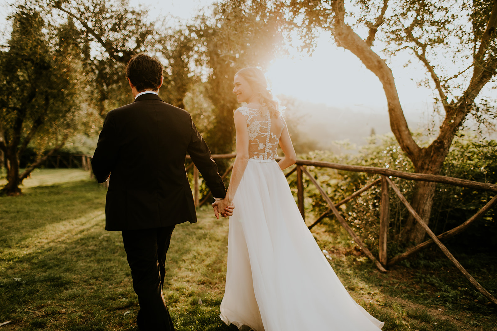 Bride and groom walking at sunset at their romantic destination wedding at La Badia di Orvieto in Italy